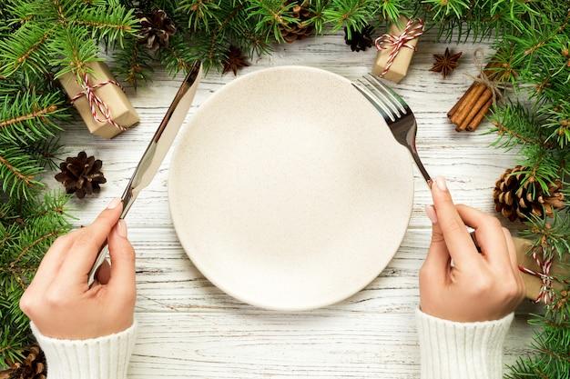 Vista superior menina mantém garfo e faca na mão e está pronto para comer