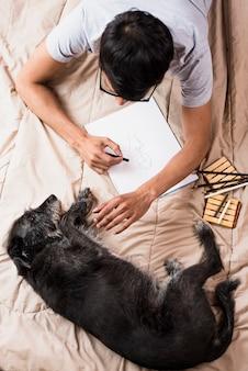 Vista superior menino desenhando com carvão com cachorro