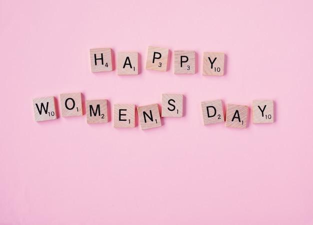 Vista superior, mensagem, feliz, woomans, dia, soletrado, em, blocos madeira, ligado, experiência cor-de-rosa