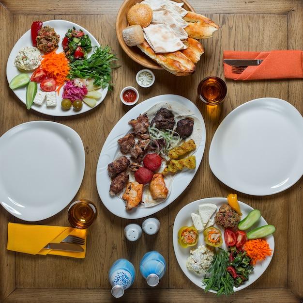 Vista superior mesa de jantar com alimentos para duas pessoas.