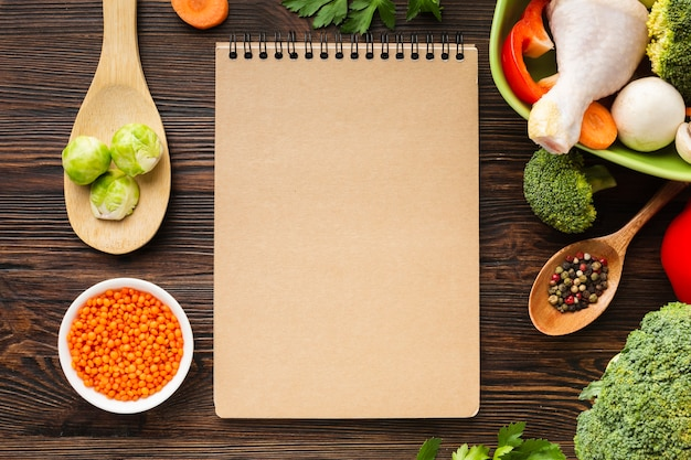 Vista superior mistura de legumes e coxa de frango na tigela com o caderno em branco