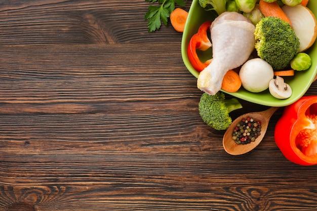 Vista superior mistura de legumes e coxa de frango na tigela e colher de pau, com espaço de cópia