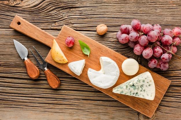 Vista superior mistura de queijo gourmet na tábua de madeira com uvas e utensílios