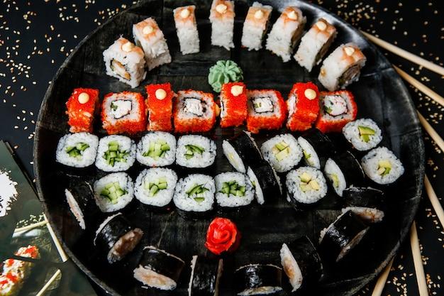 Vista superior misture rolos de sushi em um prato com wasabi e gengibre