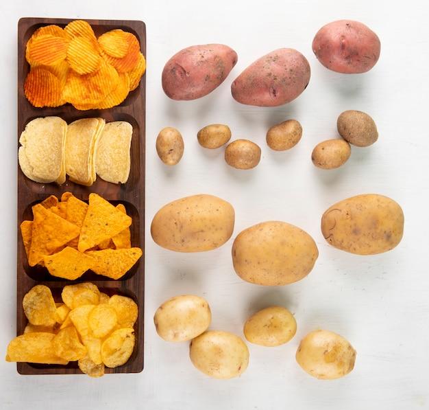 Vista superior mix chips de milho paprika chips de batata frita nachos e batata crua no fundo branco