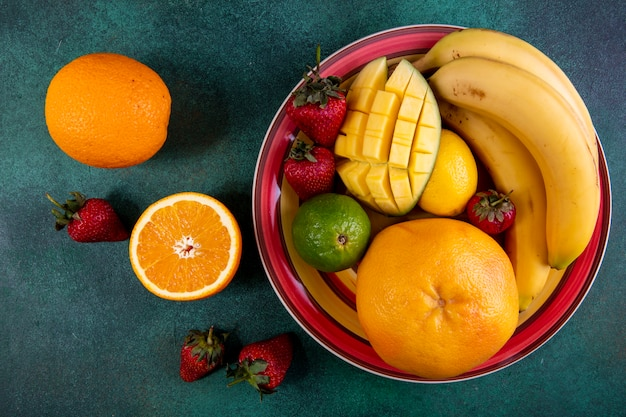 Vista superior mix de frutas em um prato de manga morango limão e laranja em verde