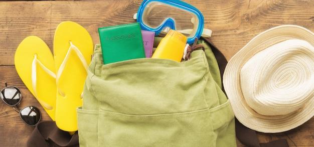 Vista superior mochila e viajante acessórios na mesa de madeira. conceito de viagens