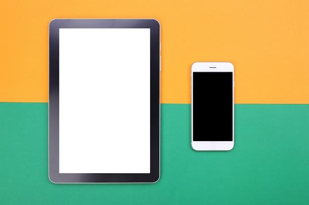 Vista superior mockup tablet e smartphone em fundo pastel verde e laranja