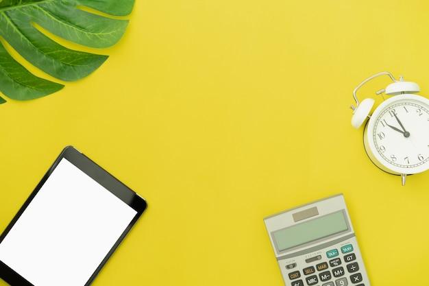 Vista superior moderna digital tablet e calculadora com despertador amarelo