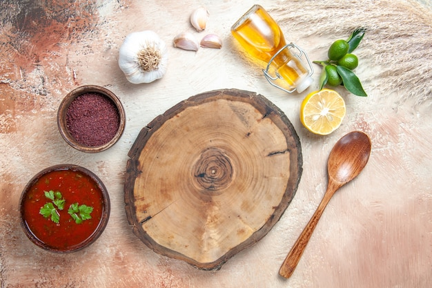 Vista superior molho de madeira tábua de limão garrafa de óleo molho de especiarias colher