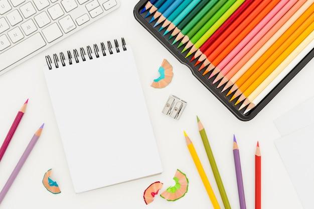 Vista superior monte de lápis coloridos com bloco de notas