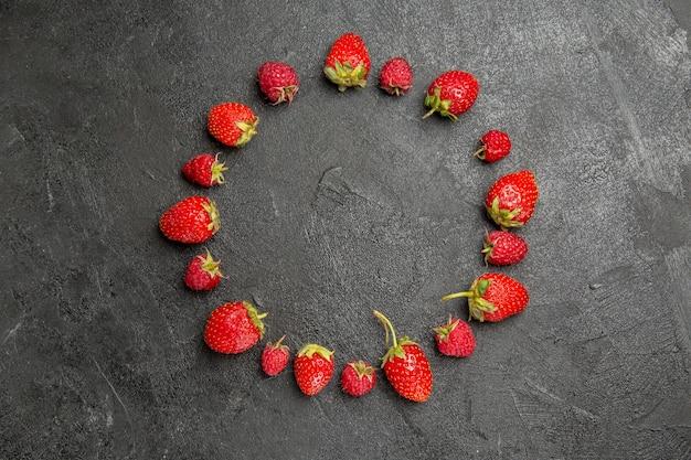 Vista superior, morangos frescos e vermelhos, alinhados com frutas silvestres de cor cinza-escuro