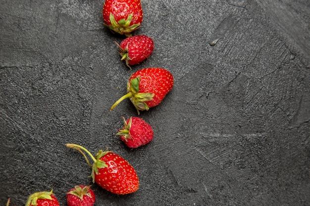 Vista superior, morangos frescos e vermelhos, alinhados com frutas vermelhas da cor escura da mesa