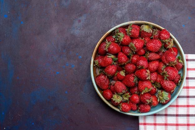 Vista superior, morangos vermelhos frescos, bagas maduras dentro de uma tigela redonda no fundo escuro.