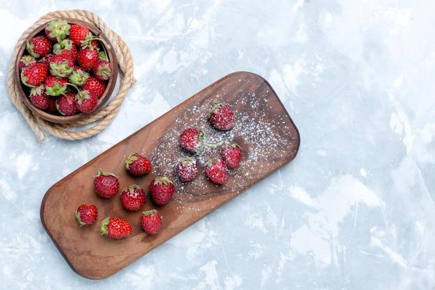 Vista superior, morangos vermelhos frescos e bagas suaves em uma mesa branca clara