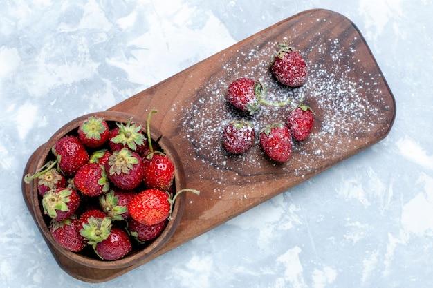 Vista superior, morangos vermelhos frescos e frutas silvestres suaves na mesa de luz
