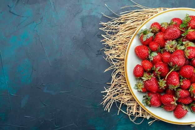 Vista superior, morangos vermelhos frescos, frutas suaves, bagas, dentro do prato, fundo azul escuro.