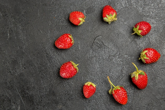 Vista superior, morangos vermelhos frescos na mesa de cor escura, frutas vermelhas maduras