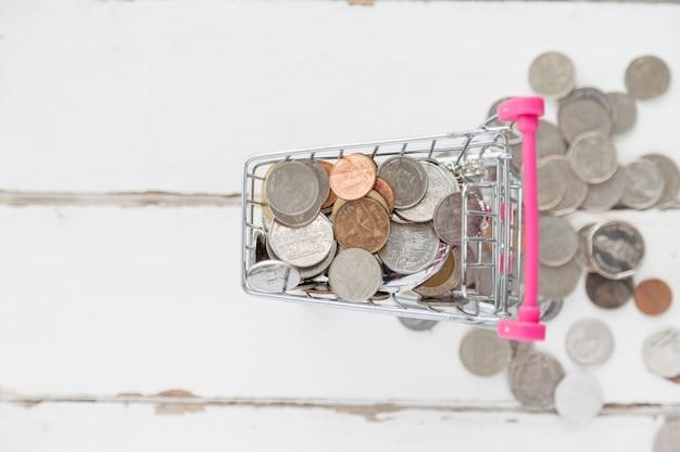 Vista superior muitas moedas no mini carrinho de compras com uma moeda cair do carrinho no assoalho de madeira branco