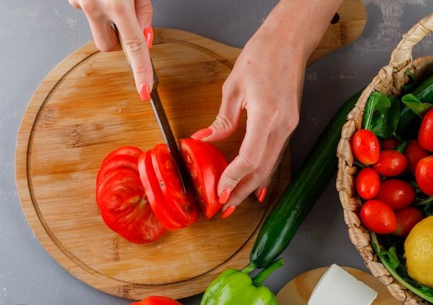 Vista superior mulher cortando tomate na tábua com pepino, pimenta verde na superfície cinza