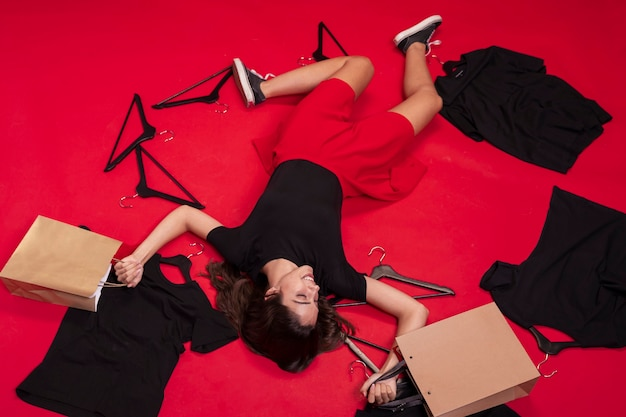 Vista superior mulher ficar no chão com suas roupas novas