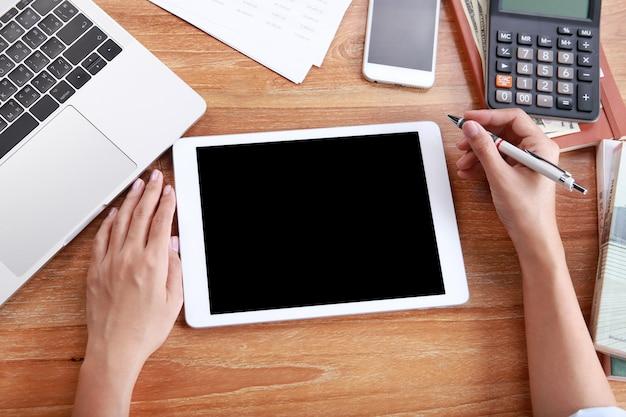 Vista superior, mulher negócio, uso, tabuleta, mockup, laptop, e, escritório, artigos papelaria, ligado, tabela madeira