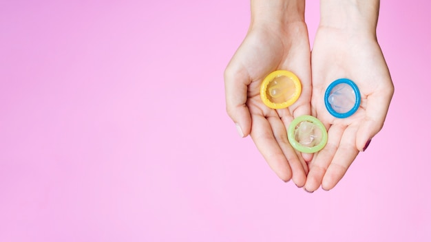 Vista superior mulher segurando preservativos coloridos