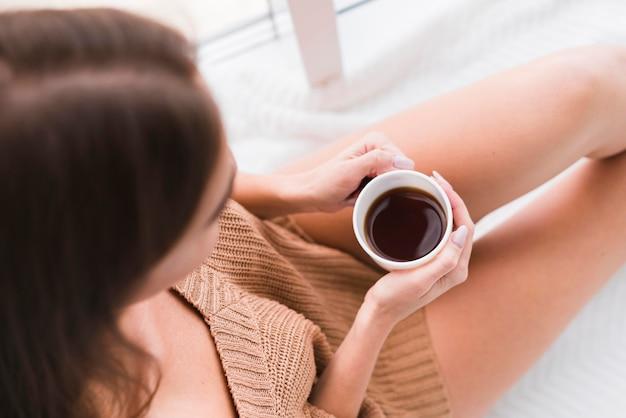 Vista superior mulher segurando uma xícara de café