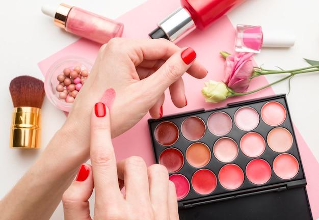 Vista superior mulher tentando produtos de maquiagem
