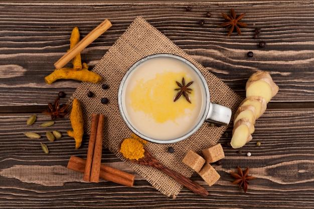 Vista superior na bebida tradicional indiana masala chai, chá com leite e especiarias na mesa de madeira.