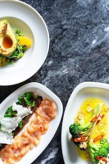 Vista superior na comida saborosa de luxo com estilo de comida de restaurante na mesa de mármore. saladas de legumes frescos e grelhados com abacate, brócolis e ceviche de robalo em chapa branca.