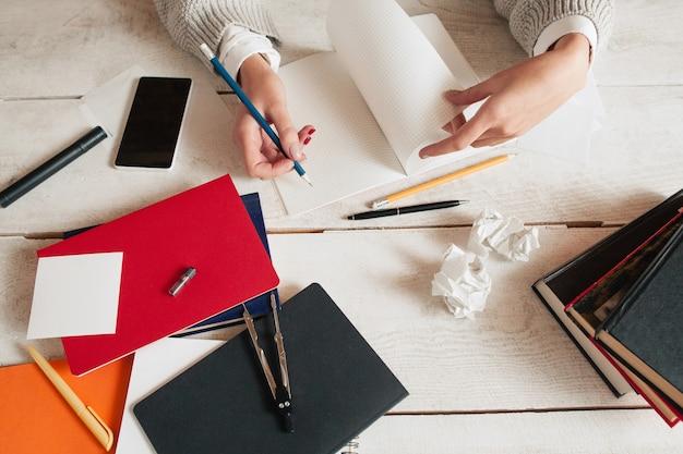 Vista superior na mão feminina, escrevendo no caderno na mesa bagunçada com suprimentos e maços de papel.