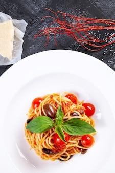 Vista superior na massa italiana tradicional com manjericão e tomate cereja em chapa branca. apartamento leigos cozinha italiana, com espaço de cópia para o projeto. macarrão mediterrâneo para o almoço.