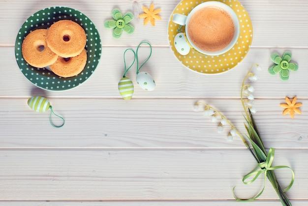 Vista superior na mesa de madeira branca com xícara de café expresso, prato de biscoitos, ovos de páscoa e flores da primavera, cópia-espaço