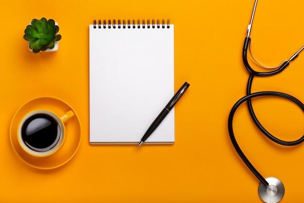 Vista superior na mesa do médico com o bloco de notas e estetoscópio