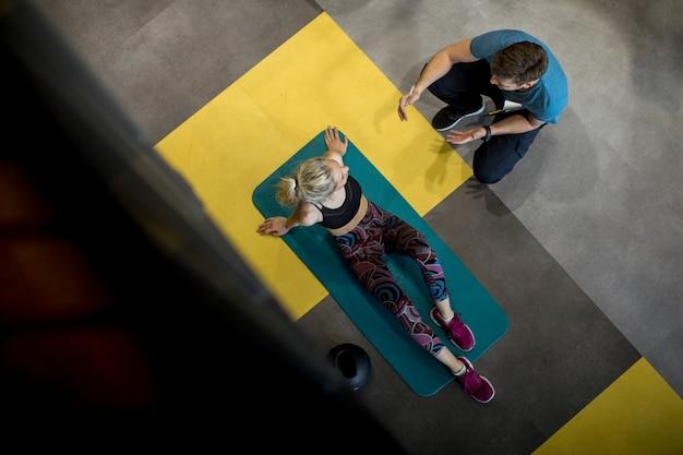 Vista superior na mulher desportiva exercícios com assistência de seu personal trainer