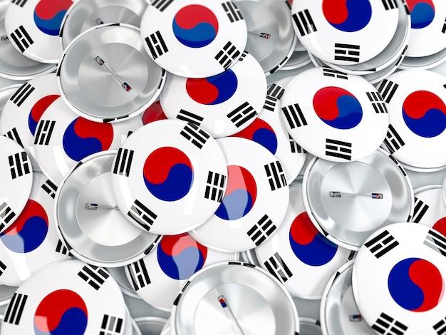 Vista superior na pilha de emblemas do botão com a bandeira da coreia do sul. renderização 3d realista