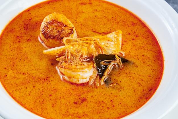 Vista superior na sopa tom yum, servida em prato branco com arroz