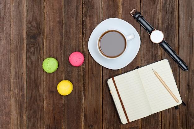 Vista superior na xícara de café, macarons, notebook e relógio.