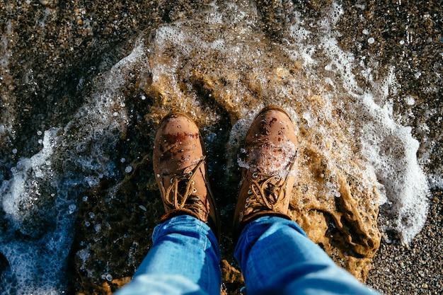 Vista superior nas botas dos homens marrons na praia de pedra, onda. fundo de pedras do mar.