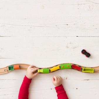 Vista superior nas mãos da criança brincando com a ferrovia e o trem de madeira colorido.