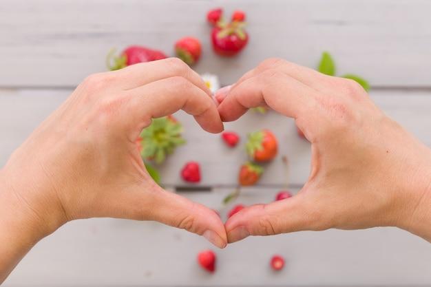 Vista superior nas mãos da mulher fazendo coração no fundo cinza mesa de morangos orgânicos frescos
