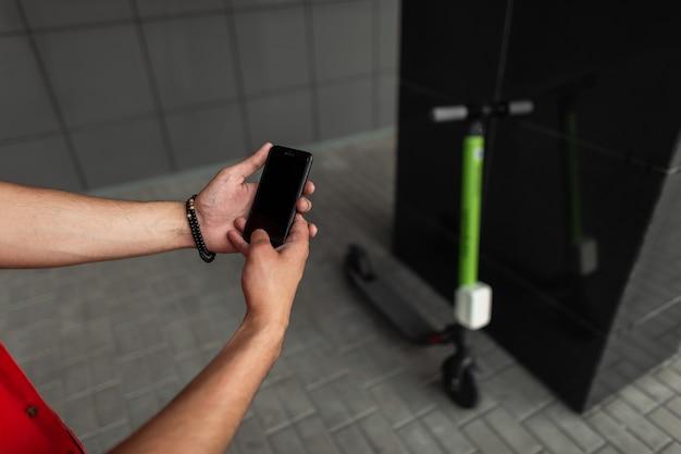Vista superior nas mãos de um jovem com um telefone celular moderno.