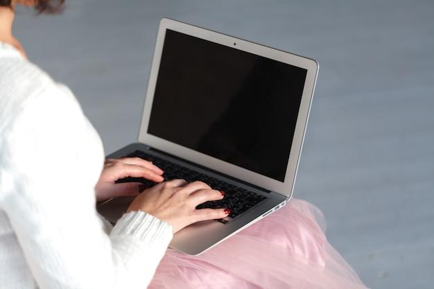 Vista superior nas mãos femininas, escrevendo no computador latop, sentado no chão de madeira.