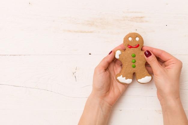 Vista superior nas mãos segurando um homem-biscoito caseiro em fundo branco de madeira