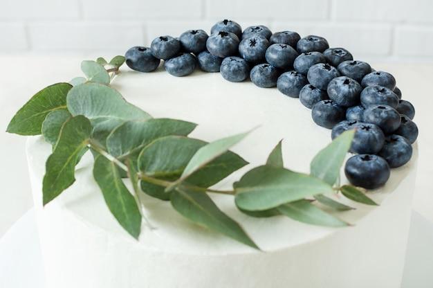 Vista superior no bolo branco com decoração de mirtilo e eucalipto.