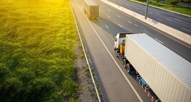 Vista superior no caminhão branco na estrada da rodovia com contêiner, conceito de transporte., importação, exportação logística industrial transporte transporte terrestre na via expressa. movimento desfocado para foco suave