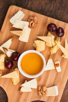 Vista superior no conjunto de queijo parmesão, mussarela, camembert e uma xícara de azeite em uma placa de madeira