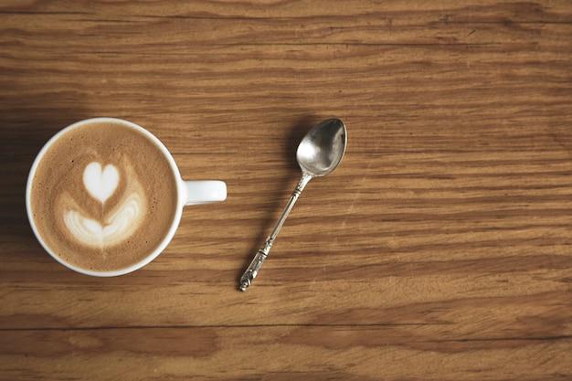 Vista superior no copo branco em branco com cappuccino com colher de prata na mesa de madeira brutal grossa na loja de café. espuma com formato de coração. concentre-se no copo superior