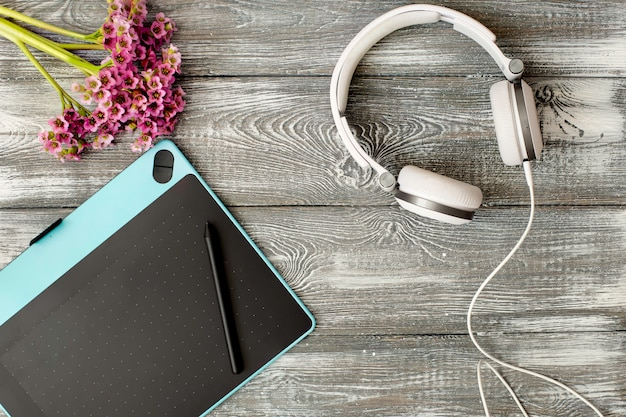 Vista superior no local de trabalho com tablet digital e caneta gráfica, fones de ouvido e flor